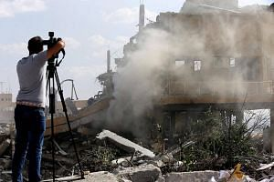 A journalist films the wreckage of a building described as part of the Scientific Studies and Research Centre compound in the Barzeh district, north of Damascus, during a press tour on April 14, 2018.