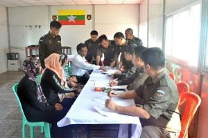 Myanmar immigration officials hand over identification documents to an unidentified Rohingya woman belonging to the five-member Rohingya family at the repatriation camp at Taungpyoletwei town in Maungdaw, near the Bangladesh border on April 14, 2018.