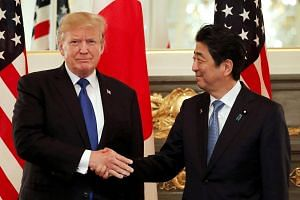 A file photo of US President Donald Trump and Japan's Prime Minister Shinzo Abe shaking hands before a working lunch at Akasaka Palace in Tokyo, Japan, on Nov 6, 2017.