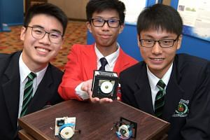(From left) Raffles Institution student Lim Zinn-E, River Valley High School student Hubert Choo and Raffles Institution student Jerald Siah with their Reaction Wheel Actuator for All Terrain Locomotion robots.