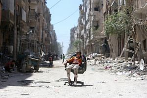 A boy sits on a chair along a damaged street at the city of Douma, Syria, on April 16, 2018.
