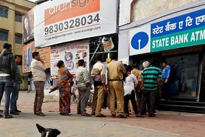 File photo showing people queuing outside an ATM to withdraw cash in Kolkata, India.