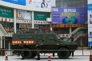 File photo showing security personnel standing in front of an armoured vehicle in Kashgar, Xinjiang, China, on March 24, 2017.