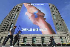 Pedestrians walk past a banner showing two hands shaking to form the shape of the Korean Peninsula, at Seoul City Hall on April 18, 2018.
