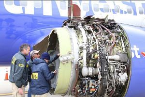 NTSB investigators examine damage to the engine of the Southwest Airlines plane.