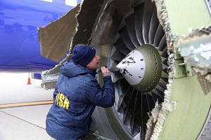 An NTSB investigator examining damage to the engine of the Southwest Airlines plane on April 17, 2018.