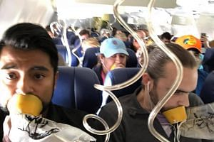 Marty Martinez posted a photo on Facebook of himself and his fellow passengers wearing oxygen masks around their mouths, but not their noses.