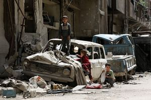 Syrian boys play on a destroyed car in the former rebel-held Syrian town of Douma on April 19, 2018.