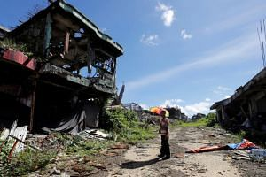 A man stands in front of his ruined house in the city of Marawi, on April 19, 2018.