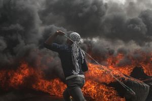 A Palestinian protester throws stones during clashes near the border with Israel, April 20, 2018.