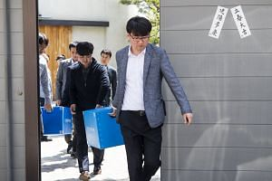 Officials of the Korea Customs Service exit the residence of Cho Hyun Min, senior vice-president of Korean Air, in Seoul, on April 21, 2018.