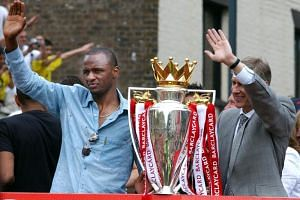 Arsenal team captain Patrick Vieira and manager Arsene Wenger wave from the open-top bus with their Premier League trophy in London on May 16, 2004.