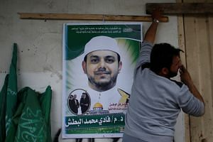 A man hangs a poster depicting Palestinian professor and Hamas member Fadi Mohammad al-Batsh, who was shot to death in Malaysia, on his family house in the northern Gaza Strip on April 21, 2018.