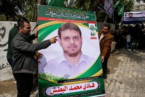 Men holding up a poster portrait of Palestinian professor and Hamas member Fadi Mohammad al-Batsh who was killed in Malaysia outside his family's house in Jabalia in the northern Gaza strip, on April 21, 2018.