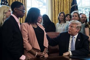 US President Donald Trump speaks to Yvonne Ambrose, whose daughter was murdered, before signing the Allow States and Victims to Fight Online Sex Trafficking Act of 2017 in the Oval Office at the White House in Washington, DC, on April 11, 2018.