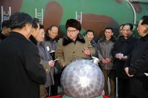 North Korean leader Kim Jong Un speaking with scientists and technicians involved in the research of nuclear weapons, in an undated picture released by the North Korean Central News Agency.