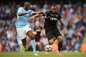 Manchester City's Ivorian midfielder Yaya Toure (left) vies with Swansea City's Ghanaian striker Jordan Ayew during the match between Manchester City and Swansea at the Etihad Stadium in Manchester, north west England, on April 22, 2018.