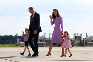 Prince William, Duke of Cambridge, walks with his wife Kate, son Prince George and daughter Princess Charlotte at the airfield in Hamburg Finkenwerder, Germany, on July 21, 2017.