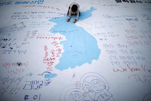 A child writes a message on a unification flag, wishing for a successful inter-Korean summit during a rally in central Seoul, South Korea, on April 21, 2018.