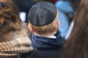 A young boy wearing a kippa during a  concentration camp memorial service in Germany on April 15, 2018.