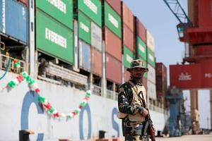 A soldier stands guard beside the Cosco Wellington, the first container ship to depart after the inauguration of the China-Pakistan Economic Corridor port in Gwadar, Pakistan, on Nov 13, 2016.