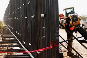 A private security guard keeps watch at the site of the construction of new bollard wall in Santa Teresa, New Mexico, as seen from the Mexican side of the border in San Jeronimo, on the outskirts of Ciudad Juarez, Mexico on April 17, 2018.