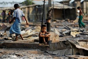 A boy sits in a burnt area after fire destroyed shelters at a camp for internally displaced Rohingya Muslims in the western Rakhine State near Sittwe, Myanmar on May 3, 2016.