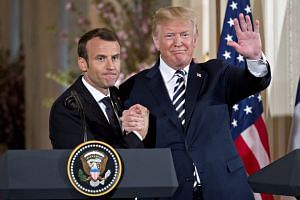 US President Donald Trump (right) waves while embracing French President Emmanuel Macron at a news conference at the White House during a state visit in Washington, DC, US, on April 24, 2018.