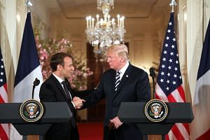 US President Donald Trump and French President Emmanuel Macron shake hands during a joint press conference, on April 24, 2018.