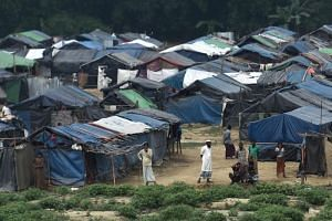 Rohingya refugees gather near their shelters in the