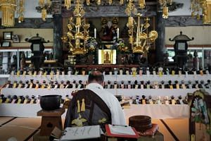 Kofukuji temple chief priest Bungen Oi offers a prayer for Sony's Aibo robot dogs, displayed on an altar prior to hold the robots' funeral, at the Kofukuji temple in Isumi, Japan, on April 26, 2018.