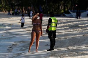 A policeman asks a tourist to leave the beach during the shutdown of the holiday island of Boracay, on April 26, 2018.