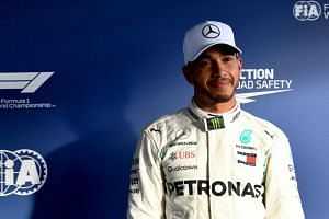 British Formula One driver Lewis Hamilton of Mercedes AMG GP stands in front of the media wall after finishing first in the qualifying session for the 2018 Formula One Grand Prix of Australia at the Albert Park circuit in Melbourne, Australia, on Mar
