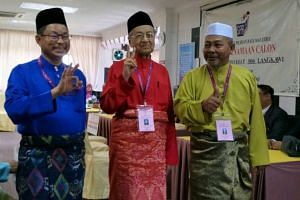 Dr Mahathir (centre) is facing a three-cornered fight against BN's incumbent MP Nawawi Ahmad (left) and Langkawi PAS chief Zubir Ahmad.