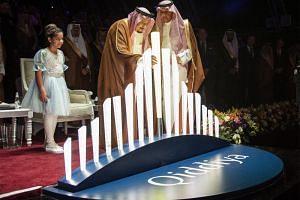 King Salman bin Abdulaziz (centre) of Saudi Arabia placing an illuminated baton in an installation for the ground-breaking ceremony of the Qiddiya entertainment city, near Riyadh on April 28, 2018.