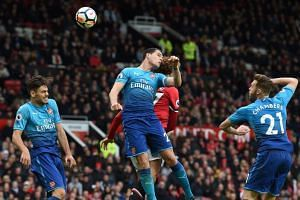 Manchester United's Belgian midfielder Marouane Fellaini (centre right) heads home their second goal under pressure from Arsenal's Swiss midfielder Granit Xhaka (centre left) during the match between Manchester United and Arsenal at Old Trafford in M