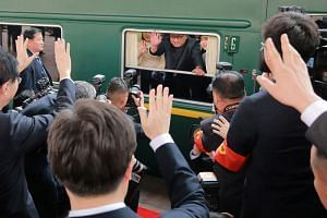 File photo released on March 28, 2018, showing North Korean leader Kim Jong Un waving from a train during an unofficial visit to China.