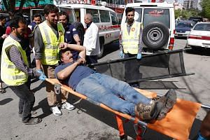 Rescuers evacuating a man who was injured in one of the explosions in the Afghan capital, Kabul, yesterday. ISIS has claimed responsibility for the two blasts.