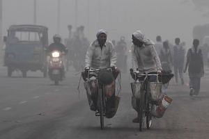 Indian commuters drive amid heavy smog in New Delhi, on Nov 7, 2017.