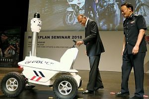 Home Affairs and Law Minister K. Shanmugam, accompanied by Commissioner of Police Hoong Wee Teck, being handed a police smartphone by the S5 Pan-Tilt-Zoom Patrol Robot at the annual police workplan seminar yesterday. The robot and special smartphone