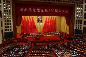 China's President Xi Jinping gives a speech during a ceremony to mark the 200th birth anniversary of German philosopher Karl Marx (pictured at top) at the Great Hall of the People in Beijing, on May 4, 2018.