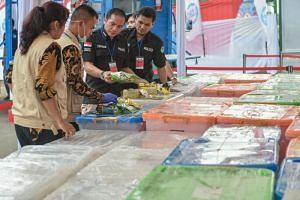Indonesian police and drugs agency members display packs of methamphetamine in Jakarta on May 4, 2018, before authorities destroyed 2.6 tons of crystal methamphetamine.