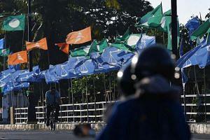 File photo showing a man cycling past party flags put up in Kota Baru, Kelantan, Malaysia.