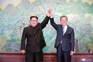 North Korean leader Kim Jong Un and South Korean President Moon Jae In pose during a signing ceremony near the end of their historic summit in the truce village of Panmunjom on April 27, 2018.