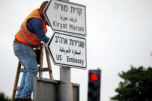 A worker hangs a road sign directing to the US embassy, in the area of the US consulate in Jerusalem on May 7, 2018.