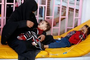 A woman sits with her sons while they are treated at a cholera treatment center in Sanaa, Yemen on Oct 8, 2017.