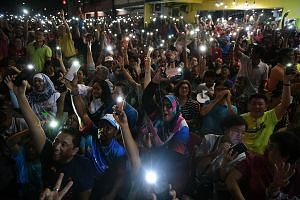 Supporters cheering for former prime minister Mahathir Mohamad, who is the chairman of opposition pact Pakatan Harapan, at a rally in Mutiara, Melaka, last Friday. A life-size hologram of Datuk Seri Najib being beamed from trucks equipped with hologr