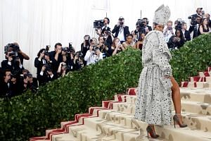 Singer Rihanna, whose bright yellow dress inspired satirical memes galore three years ago, shows up in a pimp-meets-pope outfit that looks like it fell into a vat of crystals along the way.
