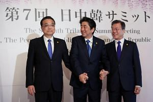 China's premier Li Keqiang (left), Japan's prime minister Shinzo Abe and South Korea's president Moon Jae In hold hands as they pose for photographs before a trilateral summit in Tokyo, Japan, on  May 9, 2018.  It is the first trilateral summit since