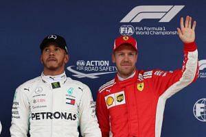 Mercedes' Lewis Hamilton celebrates pole position with Ferrari's Sebastian Vettel in third position after qualifying at the Spanish Grand Prix on May 12, 2018.